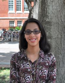 Tiffany C. Esteban smiling in front of a tree and a bike rack outside Library West.