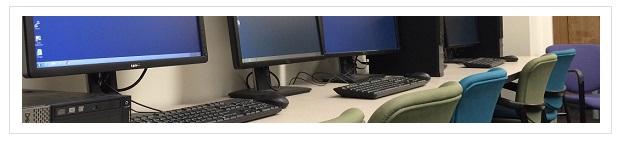 A row of computers in the Scott Nygren Scholars Studio.