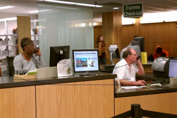 Two Library West staff members sitting at the Circulation Desk and talking to patrons on the phone