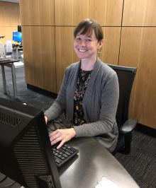 librarian sitting in front of a computer at the Library West Research Assistance Desk