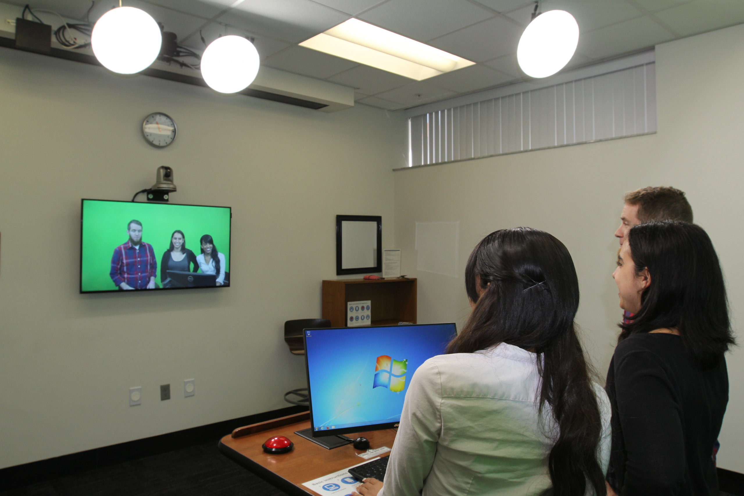 image of three students standing at the podium and recording themselves with the video recording system.