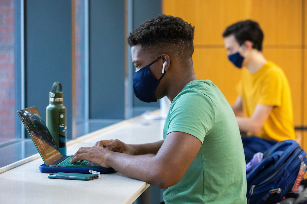 Student wearing a mask and studying with a laptop and water bottle in the first floor lounge of Library West.