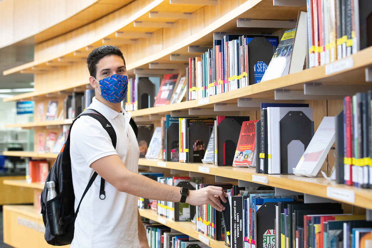 A student wearing a mask and pulling a book from the Library West New Books Wall.