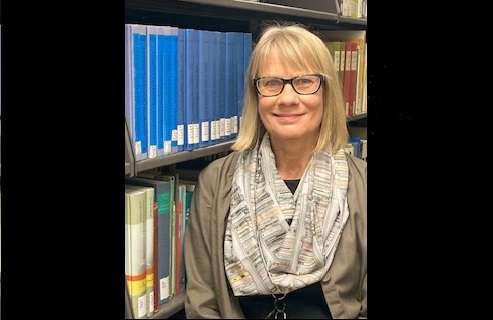 Colleen Seale smiling in front of library bookshelves